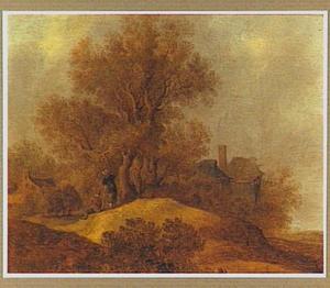 Duinlandschap met twee wandelaars bij een groep bomen