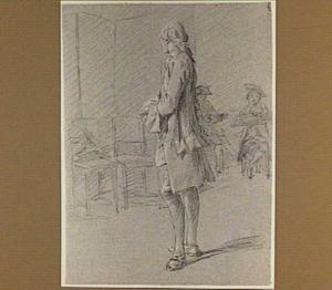 Staande man, op de achtergrond twee tekenaars