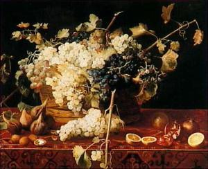 Een grote mand met druiven naast granaatappels op een