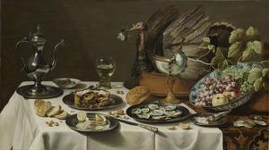 Pronkstilleven met kalkoenpastei, vruchten, oesters en pastei, kan, brood en nautilusbeker, op een oosters kleed met wit servet