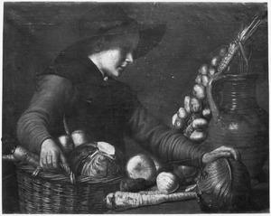 Jongen met een mand met groenten bij een tafel met een kan van rood aardewerk en nog meer groenten
