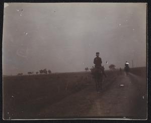 Gezicht op drie militairen te paard tijdens een militaire manoeuvre