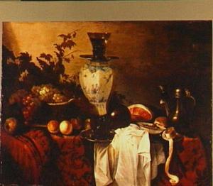 Stilleven van vaatwerk en vruchten op een tafel met een oosters kleed