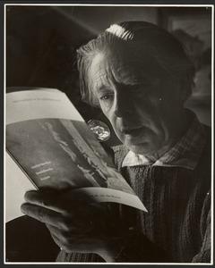 Raoul Hynckes, met een loep lezend in een kunstboek