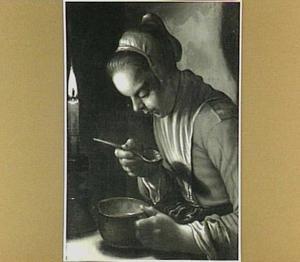 Etende vrouw bij kaarslicht