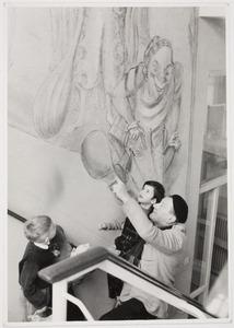 Fiedler geeft de schoolkinderen een rondleiding langs zijn wandschilderingen in de ASVO-school aan het Frederiksplein in Amsterdam.