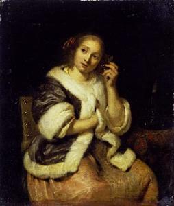 Jonge vrouw die een horloge tegen haar oor houdt