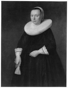 Portret van een vrouw staande met handschoenen in de rechterhand
