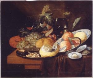 Stilleven van zuidvruchten, kreeft, garnalen en oesters, een tinnen schotel, een chinees porseleinen kom en glaswerk op een deels met een kleed bedekte tafel.