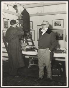 Man in historisch (19de eeuws) kostuum bij de inrichting van een tentoonstelling in Museum Fodor, 1957