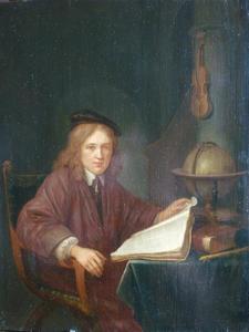 Jonge man gezeten aan een tafel met boeken en een globe