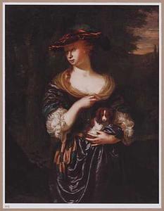 Jonge vrouw met een hondje in haar armen in een landschap