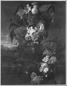 Bloemen in en rondom een tuinvaas op een muur