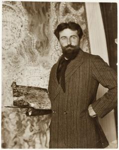 Jan Sluijters (1881-1957) staande met palet in de hand, op de achtergrond het schilderij 'Bal Tabarin'