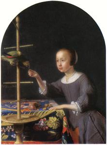 Een meisje voert een papegaai een noot