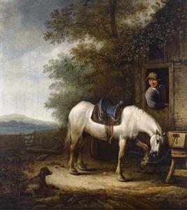 Een gezadeld paard en een hond voor een gebouw, een man leunt over de onderdeur