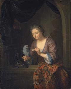 Jong vrouw voedert een papegaai in een venster