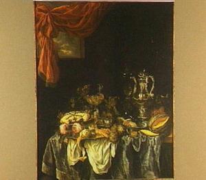 Pronkstilleven met glas- en zilverwerk, fruit, krab en kreeft, horloge en tuitkan op donker kleed met wit servet