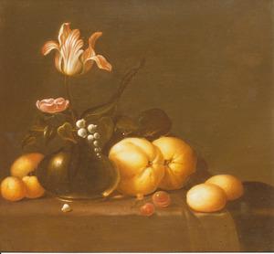Bloemen in een glazen vaas met vruchten op een gedekte tafel
