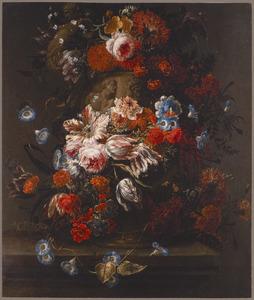 Stilleven van bloemen in en om een gedecoreerde stenen vaas op een plint