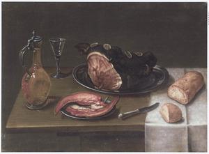 Stilleven met een bord met ham en ander vleeswaar, brood, een wijnglas en een karaf op een houten tafel