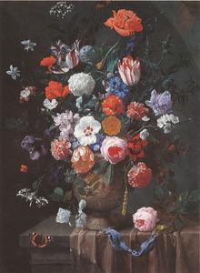 Bloemen in een gedecoreerde vaas met een horloge op een deels bedekt voetstuk