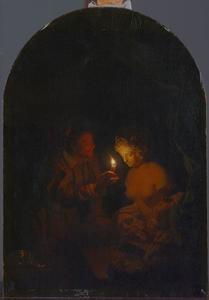 Man die een borstbeeld van een vrouw bij kaarslicht bekijkt