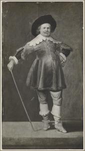 Een staande man met een wandelstok en de linkerhand in de zij