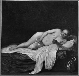 Naakte jonge vrouw liggend op een bed met een muntstuk in de hand