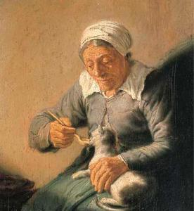 Een oude vrouw voert een kat met een lepel