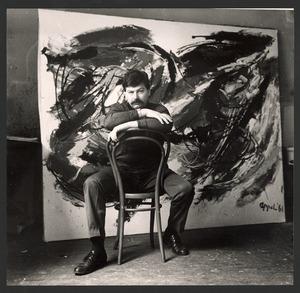 Karel Appel zittend voor een schilderij gedateerd '61'