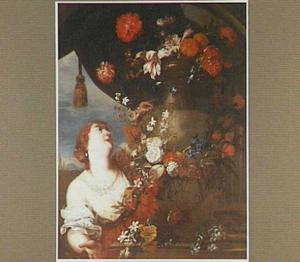 Jonge vrouw versiert een tuinvaas met bloemslingers