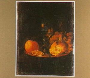 Roemer, sinaasappel, druiven en een stuk brood op een schotel