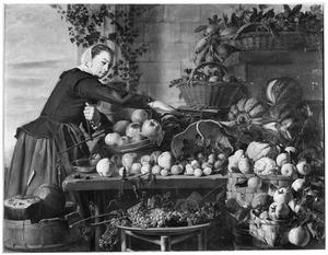 Jonge vrouw bij een uitstalling van groenten en fruit