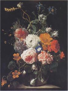 Bloemen in een glazen vaas op een stenen sokkel