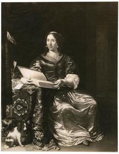 Interieur met een vrouw zittend aan tafel met een boek in de hand