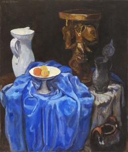 Stilleven met houten beeld, witte kan, tinnen kan en fruitschaal op met blauw kleed gedrapeerde tafel