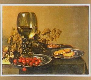 Twee roemers en tinnen borden met bessen, kersen, amandelen en brood op een tafel
