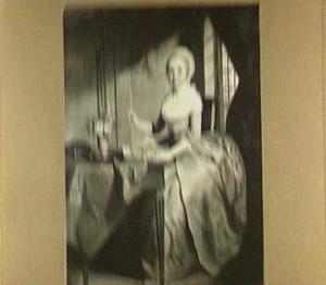 Interieur met handwerkende vrouw aan een tafel