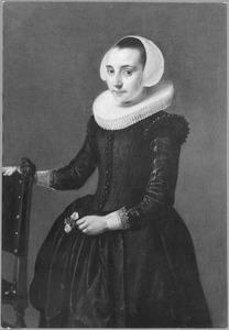 Portret van een vrouw bij een stoel, met een bloem in de hand