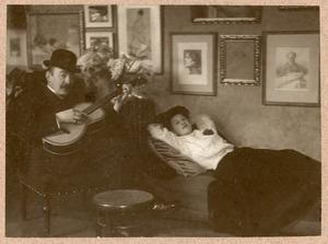 Theo van Hoytema met gitaar en het model Leentje van der Horst in het atelier van Th. Meissner