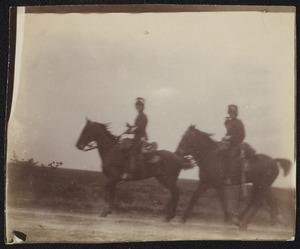 Gezicht op twee militairen te paard tijdens een militaire manoeuvre