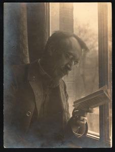 Antoon Derkinderen bij het raam, lezend in een boek