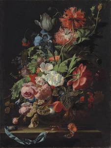 Bloemen in een metalen vaas op een stenen plint met een blauw lint en een zakhorloge