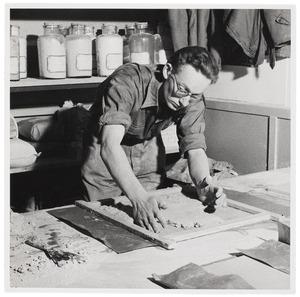 Jan Verhey, assistent van Henny Radijs, kneed platen voor een keramisch mozaïk