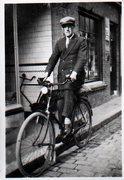 Reproductie van een foto van ene man op de fiets voor een winkel