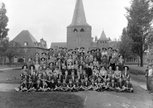 650507 - Schmidlin. De scouting van de Theresiaparochie gefotografeerd voor de parochiekerk, mei 1948. De Titus Brandsma Groep (welpen, verkenners en voortrekkers) poseren ter gelegenheid van het zilveren jubileum van pastoor G. Bannenberg (derde rij midden). De foto is gespiegeld.