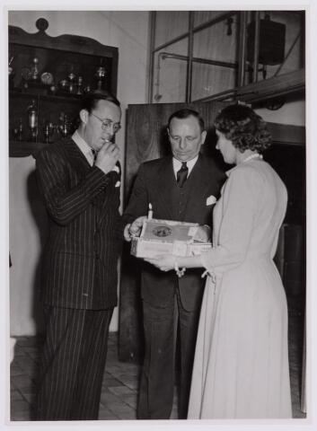037679 - Textielindustrie. Prins Bernhard krijgt een sigaar aangeboden bij zijn bezoek aan wollenstoffenfabriek H. F. C. Enneking op 13 november 1950