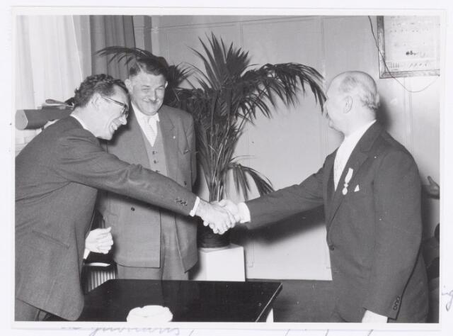 039095 - Volt. Jubileum. Op 26 oktober 1957 vierde de heer de Vries zijn 40-jarig dienstjubileum bij Volt. De jubilaris startte zijn loopbaan bij Philips in Eindhoven en kwam in 1931 naar Volt. Hij was bij Volt afdeling-chef van de Technische Voorcalculatie.  Enige tijd was hij ook voorzitter van de Volt Harmonie en vice-voorzitter van de vereniging van Chefs en Assistenten de VOCA. V.l.n.r.: Burgemeester mr. C.J.G. Becht, die een onderscheiding uitreikte, de heer J. Kipperman, directeur van Volt en de jubilaris.