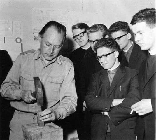 1238_F0254 - Jan Dijker (1913-1993) Hij vervaardigde veel religieuze kunst o.a. glas-in-lood Kerk en kunst in de schouwburg.  Groep jongens (vermoedelijk priesterstudenten) kijkt toe hoe Jan Dijker bezig is met een hamer.  Een van hen rookt nog. De tabaks - en rookwarenwet is van kracht sedert 1990.
